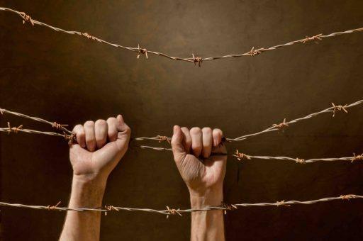 hand behind barbed wire with dark background
